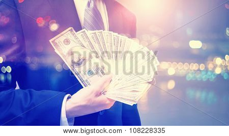 Double Exposure Of Businessman Displaying Spread Of Cash