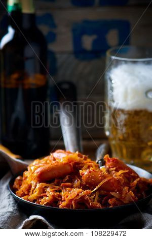 Stewed Cabbage With Sausages In A Vintage Frying Pan And A Mug With Beer.