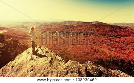 Man Standing On A Cliffs Edge Overlooking The Mountains