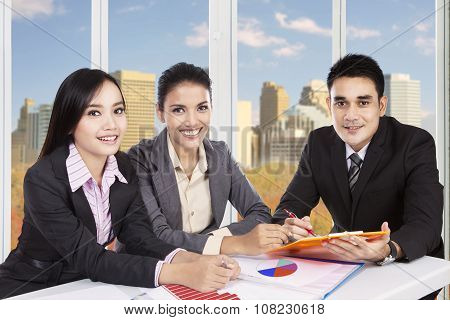 Group Of Three Workers Meeting In Office