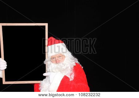 Santa Claus holds a Blank White Sign with room for your text or advertising or message. Santa Claus advertises your product or service with his blank sign while isolated on black velvet.