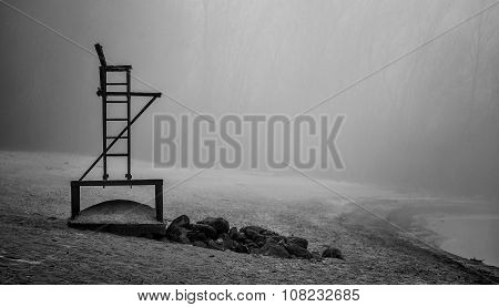 Empty lifeguard chair on a beach on a foggy November morning.
