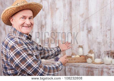 Cheerful senior farmer is presenting his work