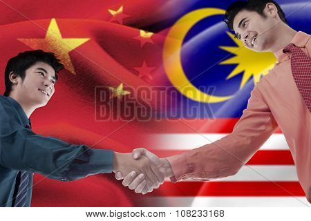 Malaysian Person Shaking Hands With Chinese Man