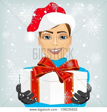 Young man wearing a santa hat offering gift
