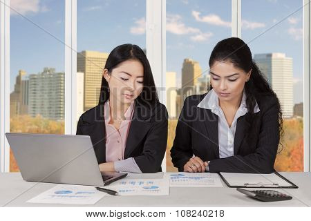 Two Multiracial Businesswomen Discussing In Office