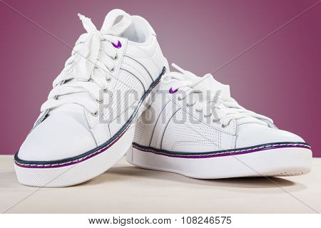 Fashion Ideas And Concepts. Fashionable Stylish White Plimsolls On Wooden Surface