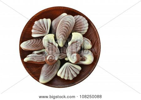 Chocolate Candies, Seashell And Seahorse Truffles On Wooden Plate Over White Background
