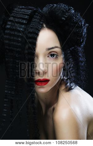 Young beautiful woman with curly hair and red lips. Glamour fashion portrait.
