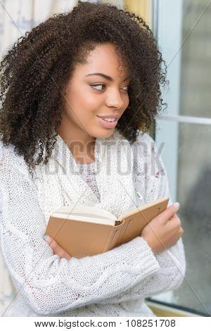 Pleasant girl enjoying reading book