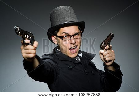 Criminal in black coat holding hadgun against gray