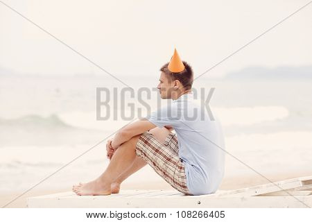 Portrait of young man wearing orange party hat, blues t-shirt and checkered shorts celebrating birthday sitting alone on deckchair with hands on his knees on beach near sea - loneliness concept