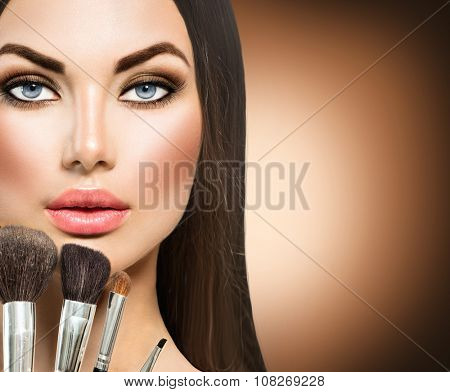 Makeup. Beauty Girl with Make up Brushes. Natural Make-up for Brunette Woman with Brown Eyes. Beautiful Face. Makeover. Perfect Skin. Applying Makeup