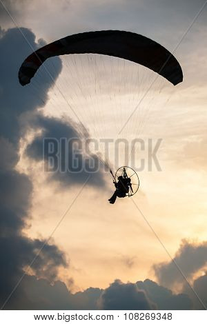 Silhouette paraglider on sunset sky background