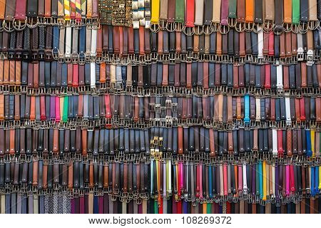 Many colored leather belts on a market. Fashion background