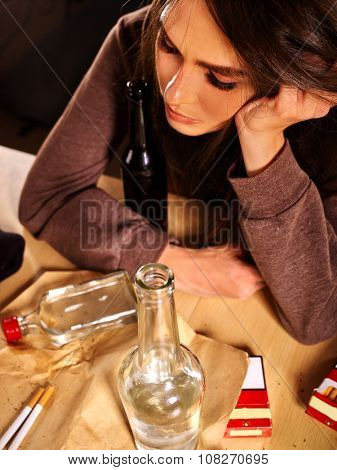 Drunk girl sitting with bottle of alcohol. Soccial issue female alcoholism.