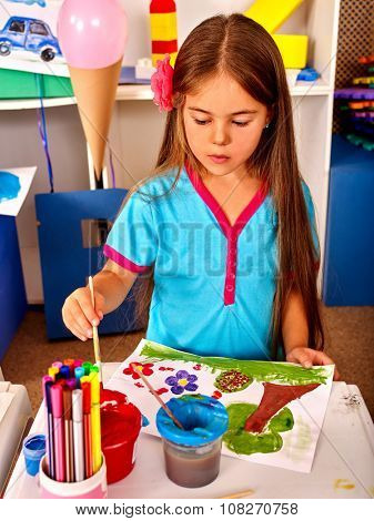 Little girl kid with brush painting on table in  kindergarten . Preschool learning.