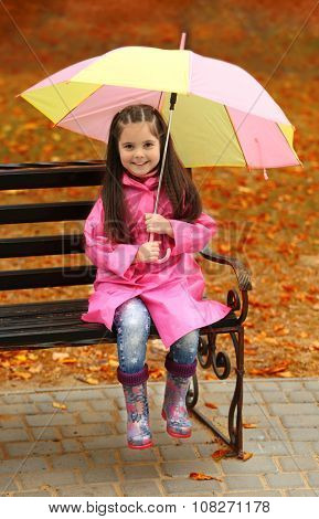 Beautiful little girl with umbrella sitting on bench in park
