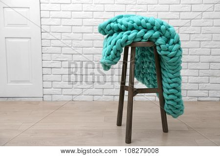 Knitted woolen blanket on chair, on home interior background