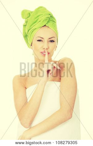 Beautiful woman with turban towel make hush gesture.