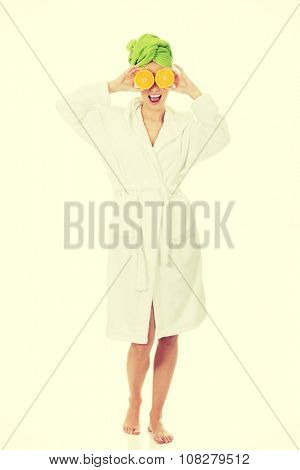 Beautiful spa woman in bathrobe with orange on eyes.
