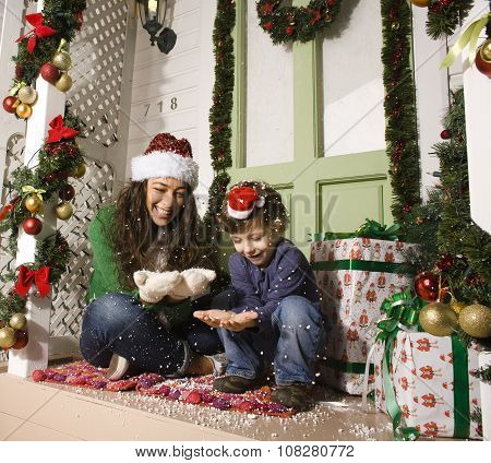 happy family on Christmas in red hats waiting gests and smiling outdoor at house, brother and sister