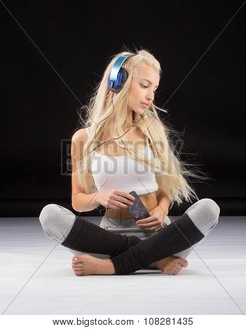 Fitness, sport, training and lifestyle concept - smiling woman sitting on the floor in lotus pose wi