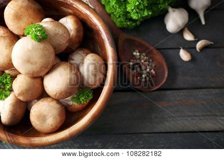 Mushrooms in wooden bowl on wooden surface