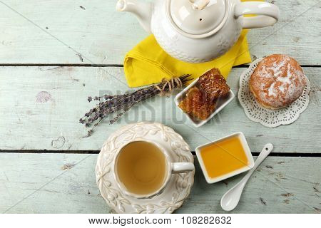 Honeycomb, bowl with honey, teapot on color wooden background