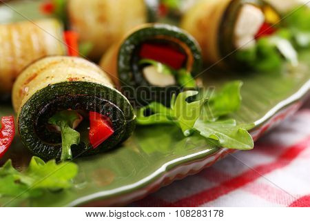 Zucchini rolls with cheese, bell peppers and arugula on plate, close-up