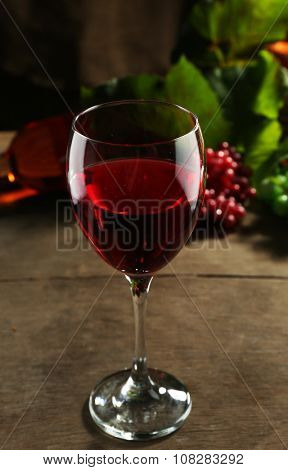 Red wine glass against wicker basket with grape and wine bottle on wooden table