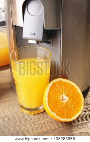Stainless juice extractor with glass of orange juice on wooden background, close up