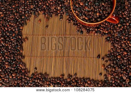 A frame of aromatic coffee beans and a cup on bamboo mat