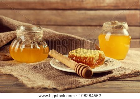 Pots of honey and honeycomb with dipper on sacking