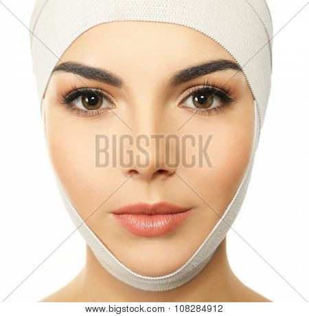 Young beautiful woman with an elastic bandage on her head, isolated on white