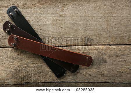 Leather bracelets on wooden background