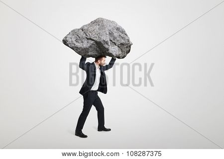young businessman carrying big stone over grey background