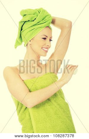 Young woman wrapped in towel using deodorant.