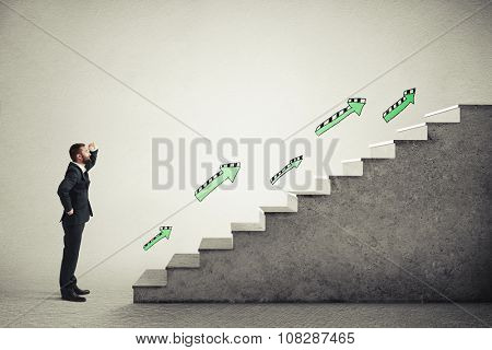 smiley businessman in formal wear standing near concrete stairs with green arrows and looking at the top over light grey background