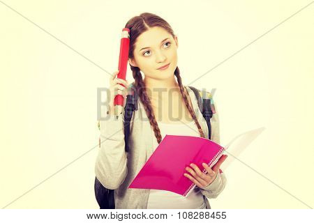 Thoughtful teen woman with pencil and notebook.