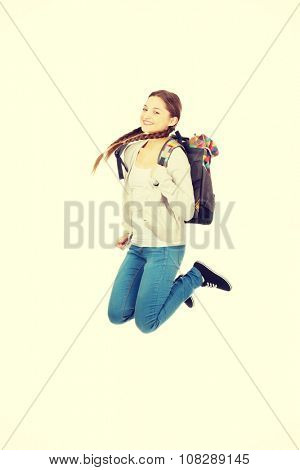 Happy teen woman jumping with backpack.