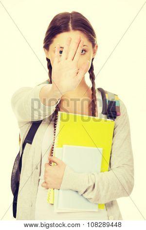 Teenager girl with school backpack make stop gesture.