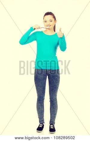 Happy teenager woman brushing teeth.