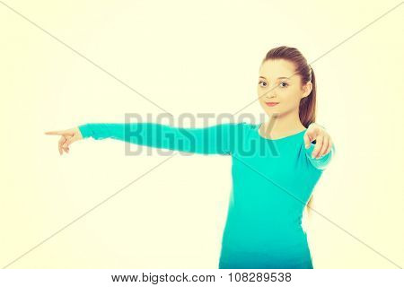 Beautiful teen woman pointing on you and aside.
