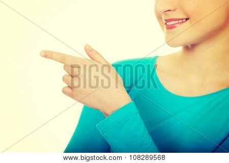 Happy beautiful young woman pointing aside.