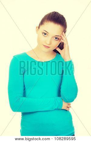 Thoughtful teenage woman touching head.