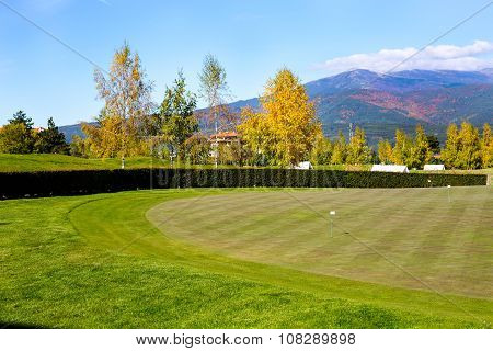 Vibrant nature  background with colorful green, yellow autumn trees, golf grass field and flags