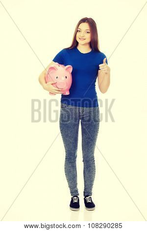 Teenage woman with piggybank and thumbs up.
