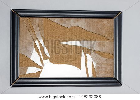 Black Picture Frame With Broken Glass Plate In Front Of Grey Background