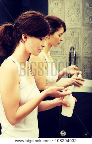 Woman cleaning hands with soap in bathroom.